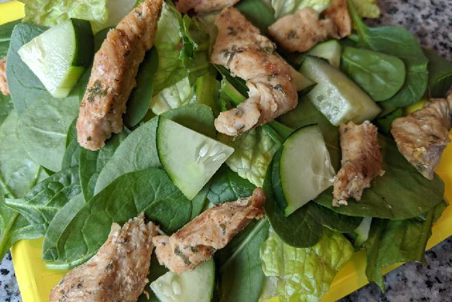 Ziołowy kurczak na liściach szpinaku i plastrach ogórka - świetna sałatka